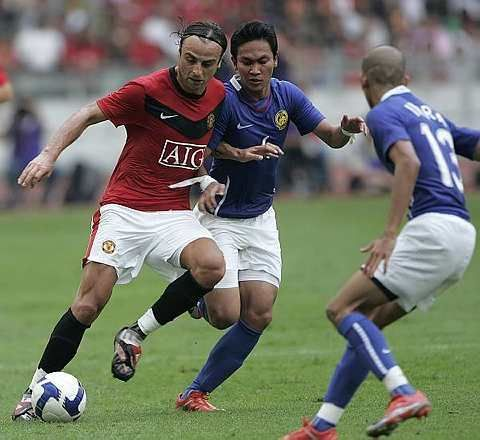 Manchester United's Dimitar Berbatov, left, is challenged by Malaysian player Mohd Asraruddin Umar, center, during a friendly match at Bukit Jalil National Stadium in Kuala Lumpur, Malaysia, Saturday, July 18, 2009