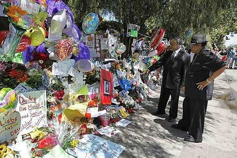 The Rev. Al Sharpton and Joe Jackson, right, the father of Michael Jackson, view a makeshift memorial outside the family home of the late pop star Michael Jackson in the Encino, Calif., June 29. - 30 June, 2009