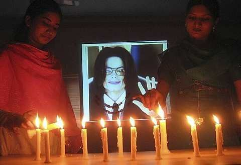 Pakistani girls light candles to pay tribute to the late King of Pop Michael Jackson in Hyderabad, Pakistan on Tuesday, July 7, 2009. - AP - 7 July, 2009