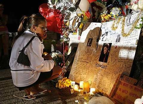 Sophia Zewdu, 32, of Las Vegas reads a card for Michael Jackson after 2 a.m. as fans continue to pay tribute at a makeshift memorial outside the Jackson family home in the Encino area of Los Angeles on Tuesday, July 7, 2009. - AP - 7 July, 2009