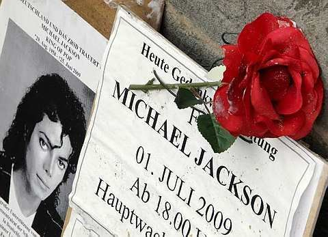 A placard and rose are seen following a commemorative gathering for late U.S. singer Michael Jackson, in front of a church in Frankfurt, central Germany, Tuesday, July 7, 2009. Michael Jackson fans around the world said Tuesday they would join in mourning the pop legend in solidarity with the thousands attending the official memorial in Los Angeles. - AP - 7 July, 2009