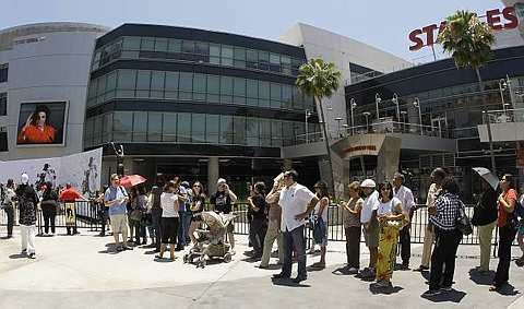 Fans wait in line to sign a large poster at the Staples Center in Los Angeles, Monday, July 6, 2009, where the memorial service for pop star Michael Jackson will be held on Tuesday. - AP - 7 July, 2009