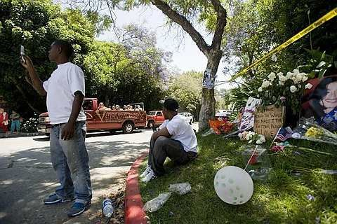 Visitors pass by a memorial outside Michael Jackson's rented home on Sunday, June 28, 2009 in the Holmby Hills section of Los Angeles. - 29 June, 2009