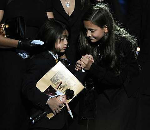 Michael Jackson II, left, and his sister Paris hold hands at the memorial service for their father music legend Michael Jackson, at the Staples Center in Los Angeles, on Tuesday, July 7, 2009.-AP - 8 July, 2009