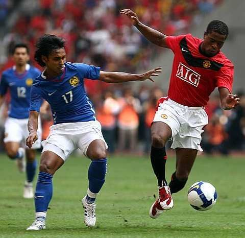 anchester United Patrice Evra tackles for the ball with Malaysia's Amri Yahya during their match at the Bukit Jalil Stadium, July 18, 2009.