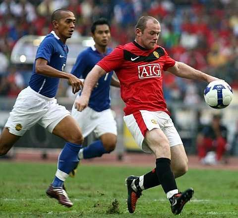 Manchester United Wayne Rooney battles for the ball with Malaysia's Norhafiz Zamani Misbah during their match at the Bukit Jalil Stadium, July 18, 2009. Manchester won 3-2