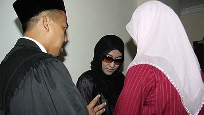 Ibu dua anak (tengah) yang didakwa berkhalwat dengan lelaki bukan Islam berbincang dengan peguamnya di Kompleks Mahkamah Syariah, Kangar. Dia ditahan ketika serbuan di sebuah hotel di sini minggu lalu yang turut dihadiri oleh suaminya.
